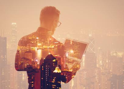 Trader mit Laptop vor Skyline